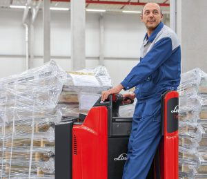 Logistics BusinessSince the launch of model series T20/T25 SP in 2004, Linde Material Handling has sold over 33,000 such pallet trucks worldwide. Linde says that this makes them the clear market leader in the platform pallet truck segment in Europe and also sets a benchmark in the field of intralogistics. Linde will be presenting a number of new, customer-oriented optional features for these successful models at its World of Material Handling (WoMH) 2016 customer event.  <br><br> Around the world, these platform pallet trucks with two or two-and-a-half tonne load capacity facilitate the loading and unloading of HGVs as well as pallet transfer and order picking. Linde's unique driving concept is key to the resounding market success: The main load of the transported goods rests on the drive wheel so that braking and acceleration forces are accurately transmitted. In addition, a hydraulic damping system with tilt sensors for the lateral support wheels ensures maximum stability and driver comfort in all situations. Whether cornering, on uneven surfaces or on slopes – the operator has full control of the vehicle and the load at all times.  <br><br>   The new equipment options enhance driver comfort, efficiency and reliability for Linde T20/T25 SP platform trucks even more. The main innovation is the completely decoupled and damped stand-on platform. Platform and steering system form a compact unit, which is decoupled from the chassis. This has led to about 30 percent reduction in jolts and vibrations – both mechanical and human.   <br><br> With this innovation, Linde takes another step towards the ergonomic unity of man and machine. This is because platform pallet trucks Linde T20/T25 SP feature proven e-Driver technology. This allows the driver to comfortably rest his back by leaning, while standing at a 45 degree angle to the direction of travel and steer the vehicle with one hand, with which he can also control all drive and lift functions. The 45-degree position prov